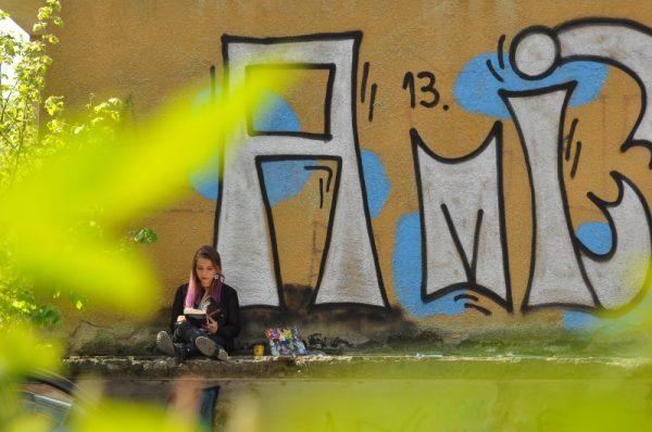 """Maria Alexandra Ţecu - """"Tinereţe"""" (Premiul special al Fotoclubului Mihai Dan Călinescu). Aşa cum spune şi titlul lucrării, tinereţea la superlativ: verdele crud al primăverii, inscripţiile tinereşti de pe zid, personajul care citeşte. O lucrare plină de culoare, în care elementele par trasate de un pictor adevărat."""
