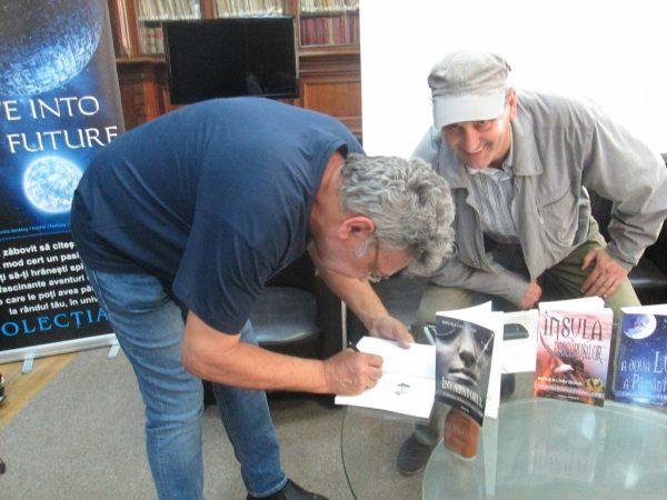 MLG dând autografe cu pixul lui Aurel Cărăşel (zâmbind malefic în planul doi).